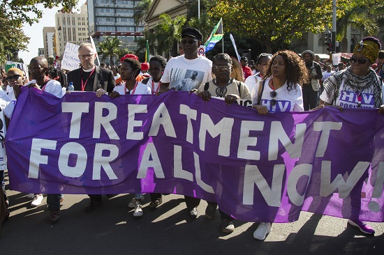 People marching with a banner reading Treatment For All Now